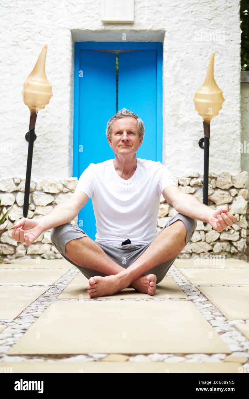 Senior Man Meditating Outdoors At Health Spa - Stock Image