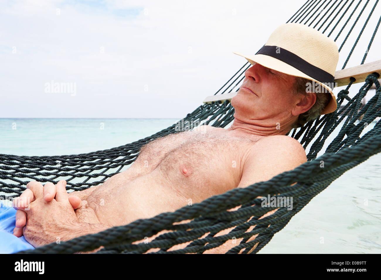 Senior Man Relaxing In Beach Hammock - Stock Image