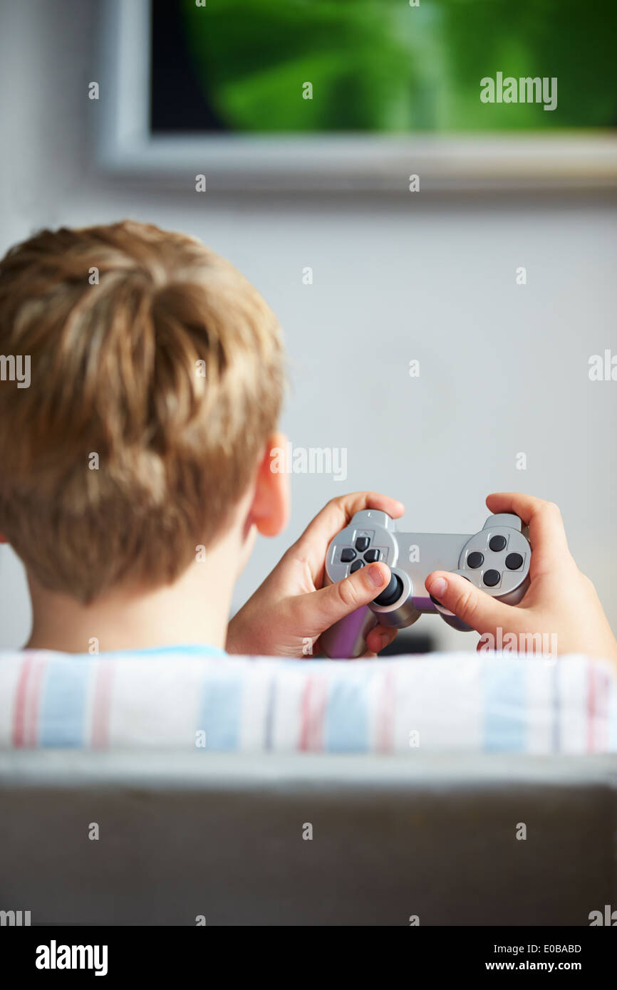 Rear View Of Boy Holding Controller Playing Video Game - Stock Image