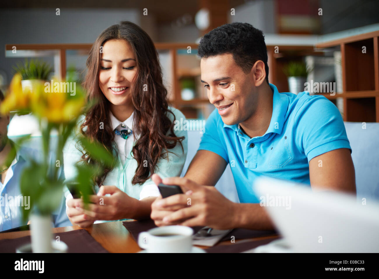 Portrait of teenage friends using cellular phones while sitting in cafe - Stock Image