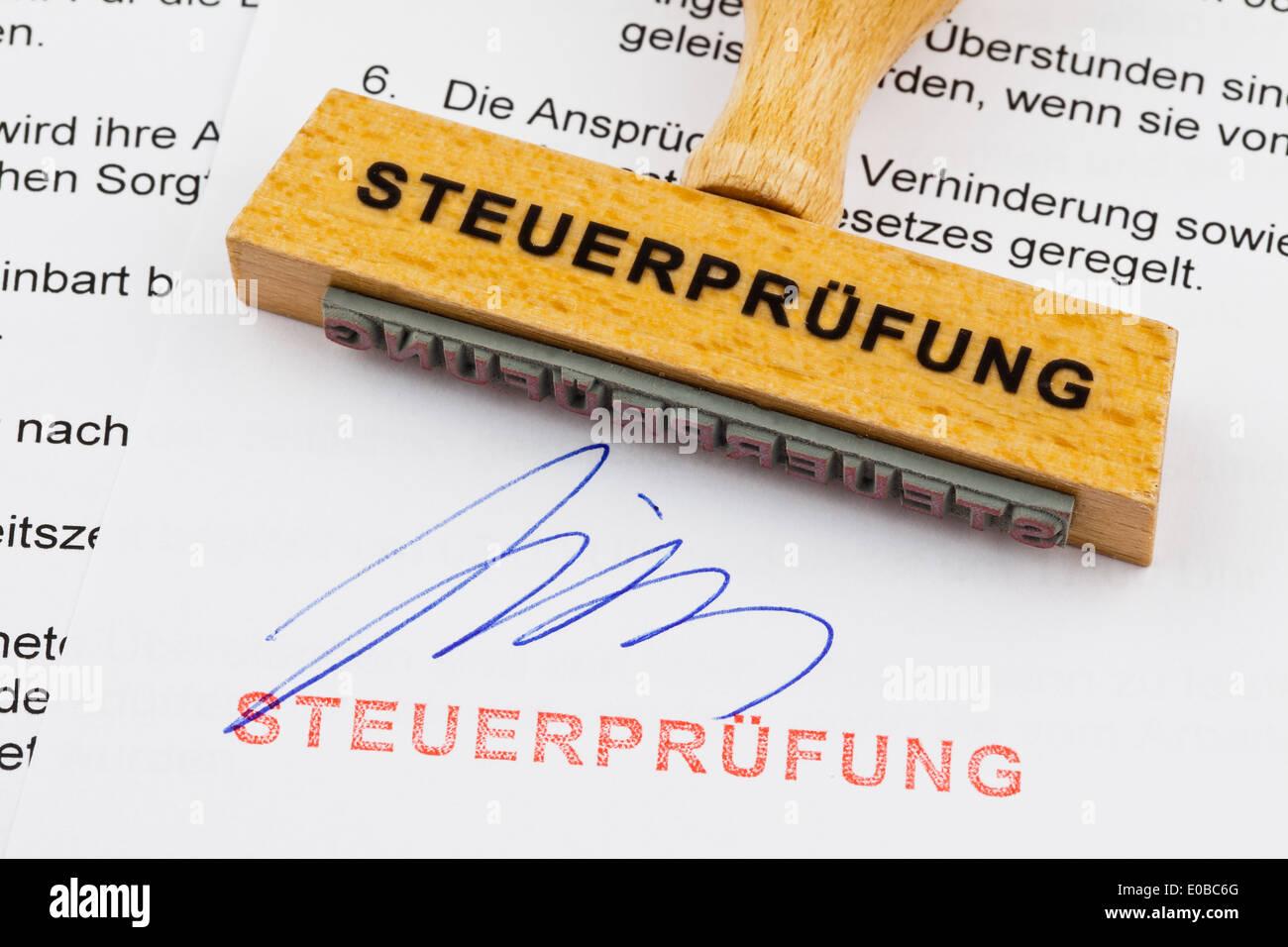 """""""A stamp of wood lies on a document. German label; tax check"""", """"Ein Stempel aus Holz liegt auf einem Dokument. Deutsche Stock Photo"""