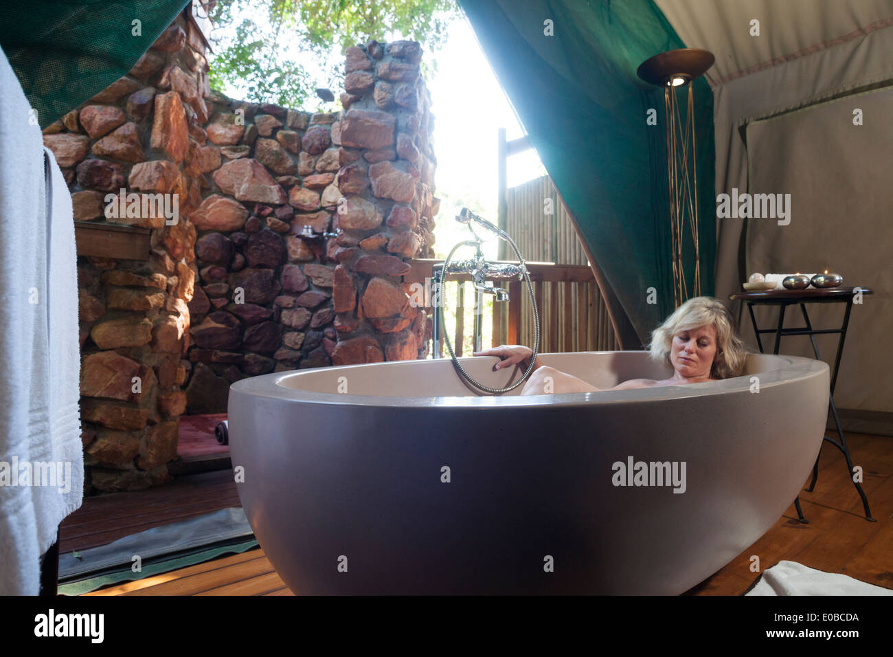 Blond woman naps inside a large oval bathtub in a luxury safari tent, Botlierskop Game Lodge, Mosselbay, South Africa - Stock Image
