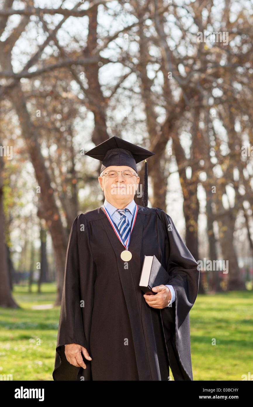 College dean in graduation gown holding a book in a park Stock Photo ...