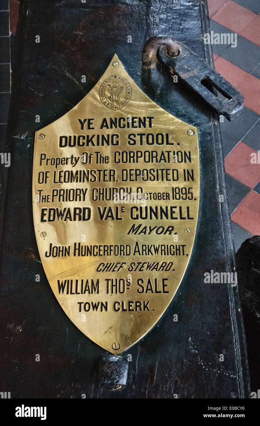 Herefordshire, UK. Sign on the old ducking stool (cucking stool) preserved in Leominster Priory Church. The last recorded use was in 1809 - Stock Image
