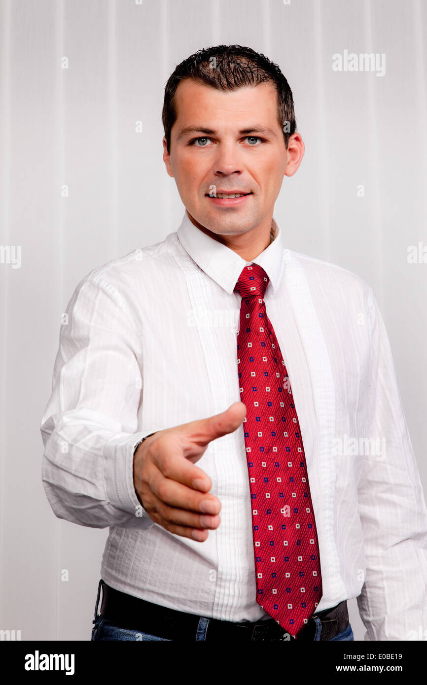 Businessman offers slap in the greeting. In the office., Geschaeftsmann bietet Handschlag zur Begruessung. Im Buero. - Stock Image