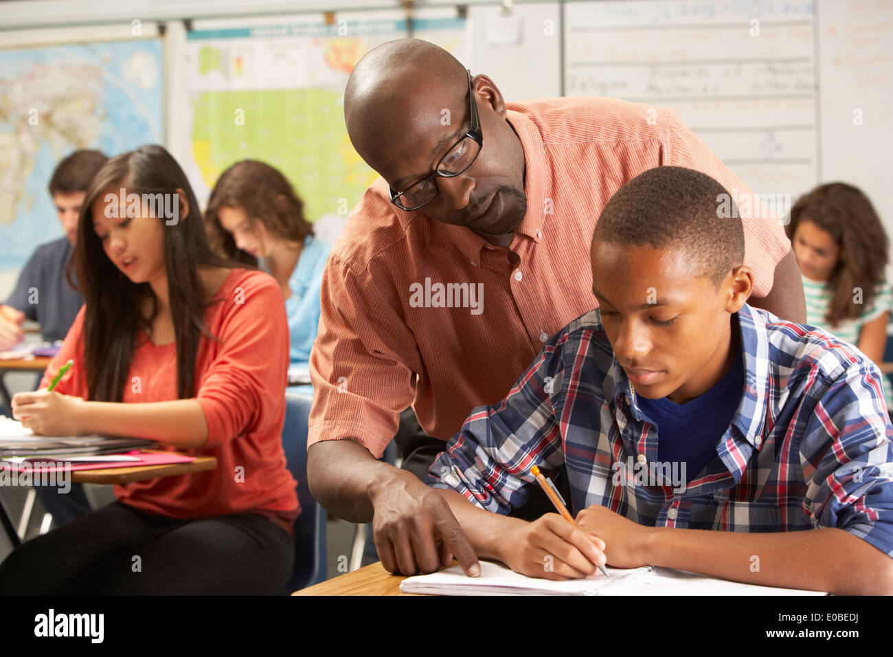 Teacher Helping Male Pupil Studying At Desk In Classroom - Stock Image