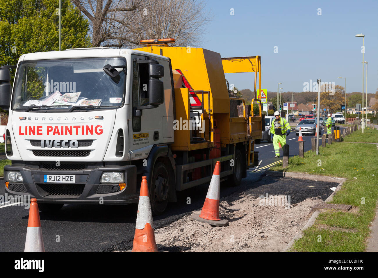 Workmen operating behind Line Painting truck. - Stock Image