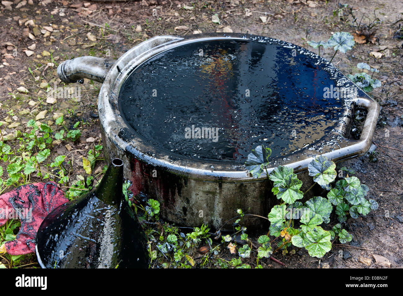 Oil drain pan overflowing, containing dirty engine oil. - Stock Image