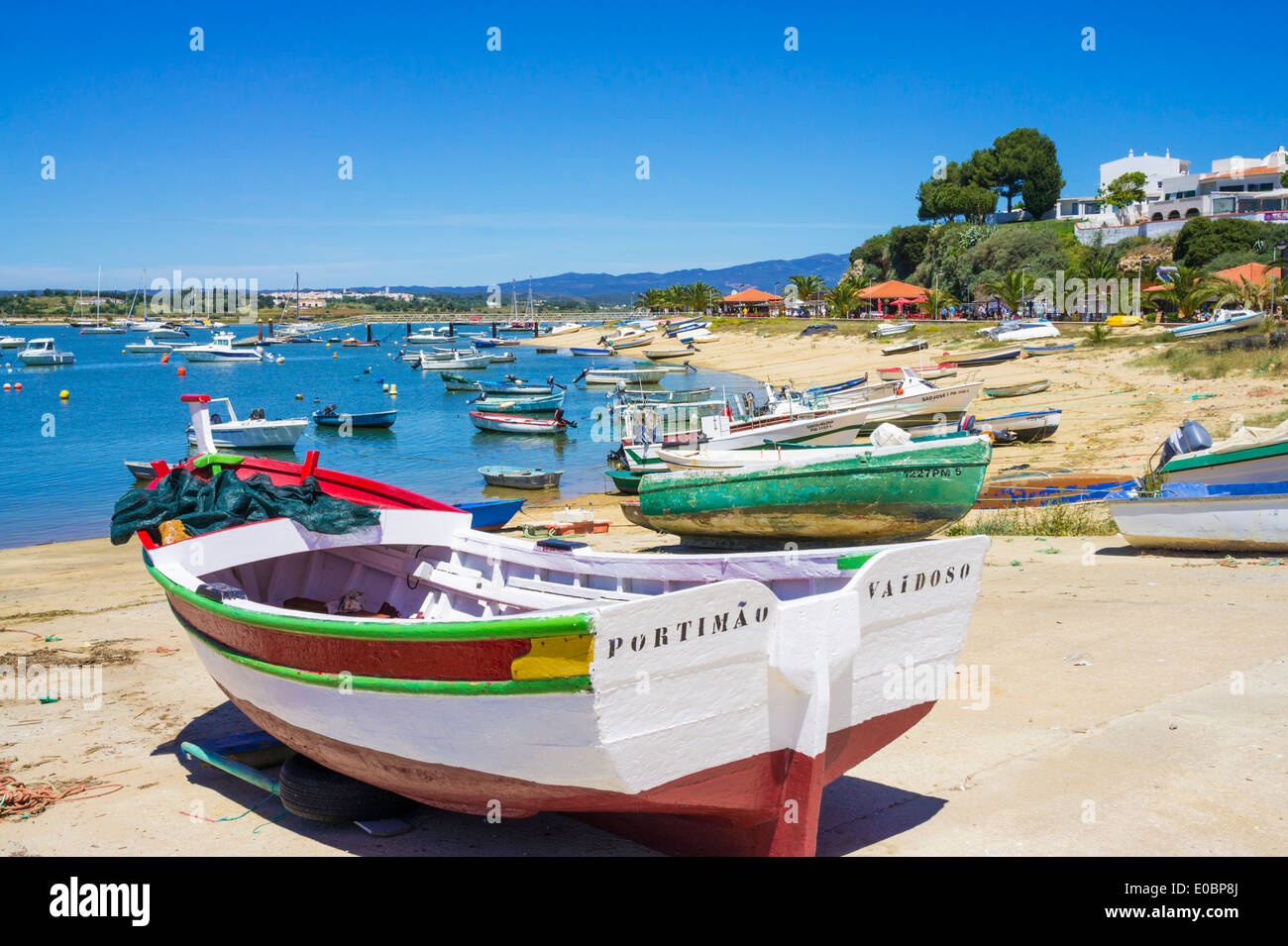 traditional painted fishing boats moored along the seafront in the village of Alvor Algarve Portugal EU Europe - Stock Image