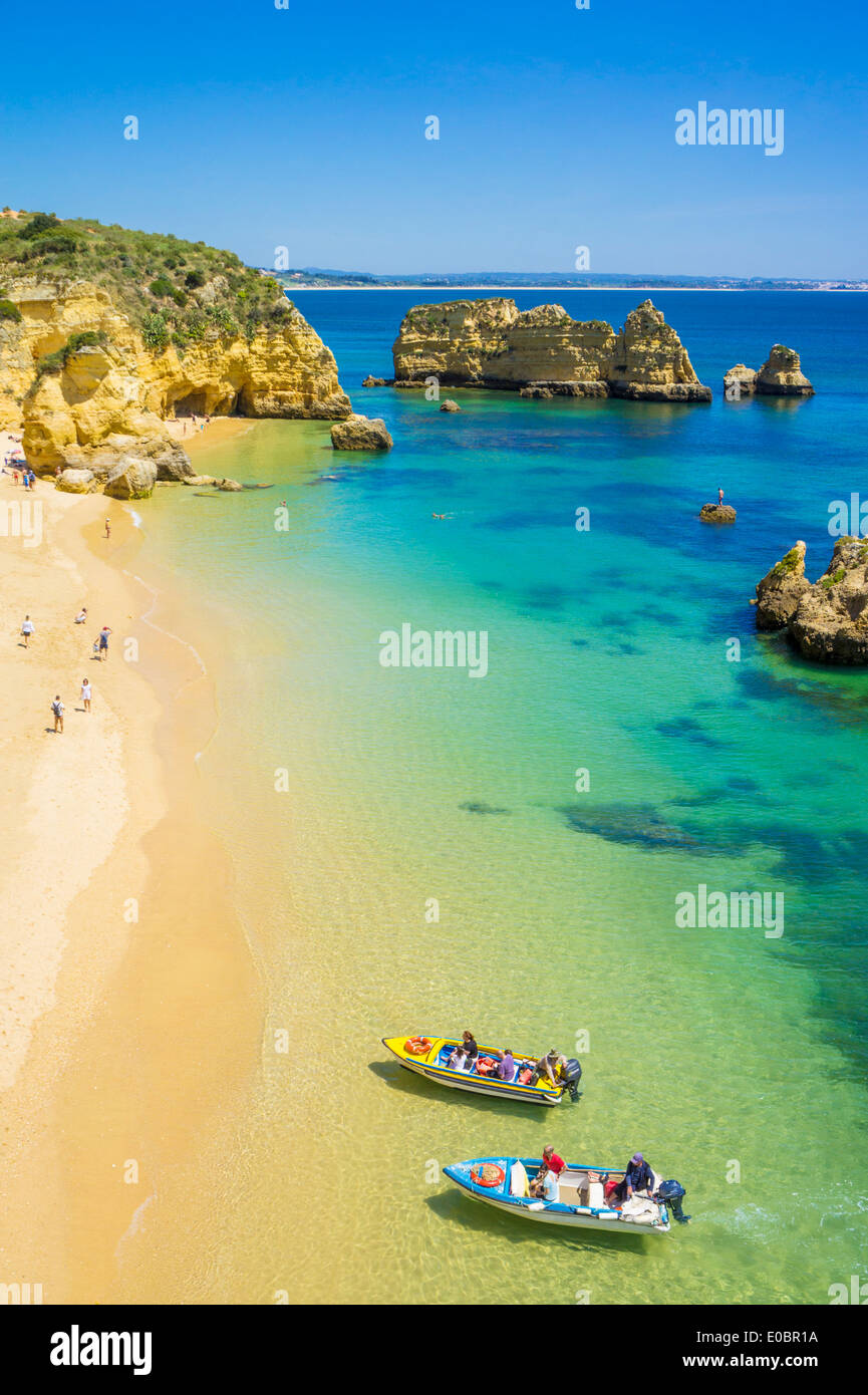 Holidaymakers and Tourist Boats at Praia da Dona Ana sandy beach near the resort of Lagos Algarve Portugal EU Europe - Stock Image