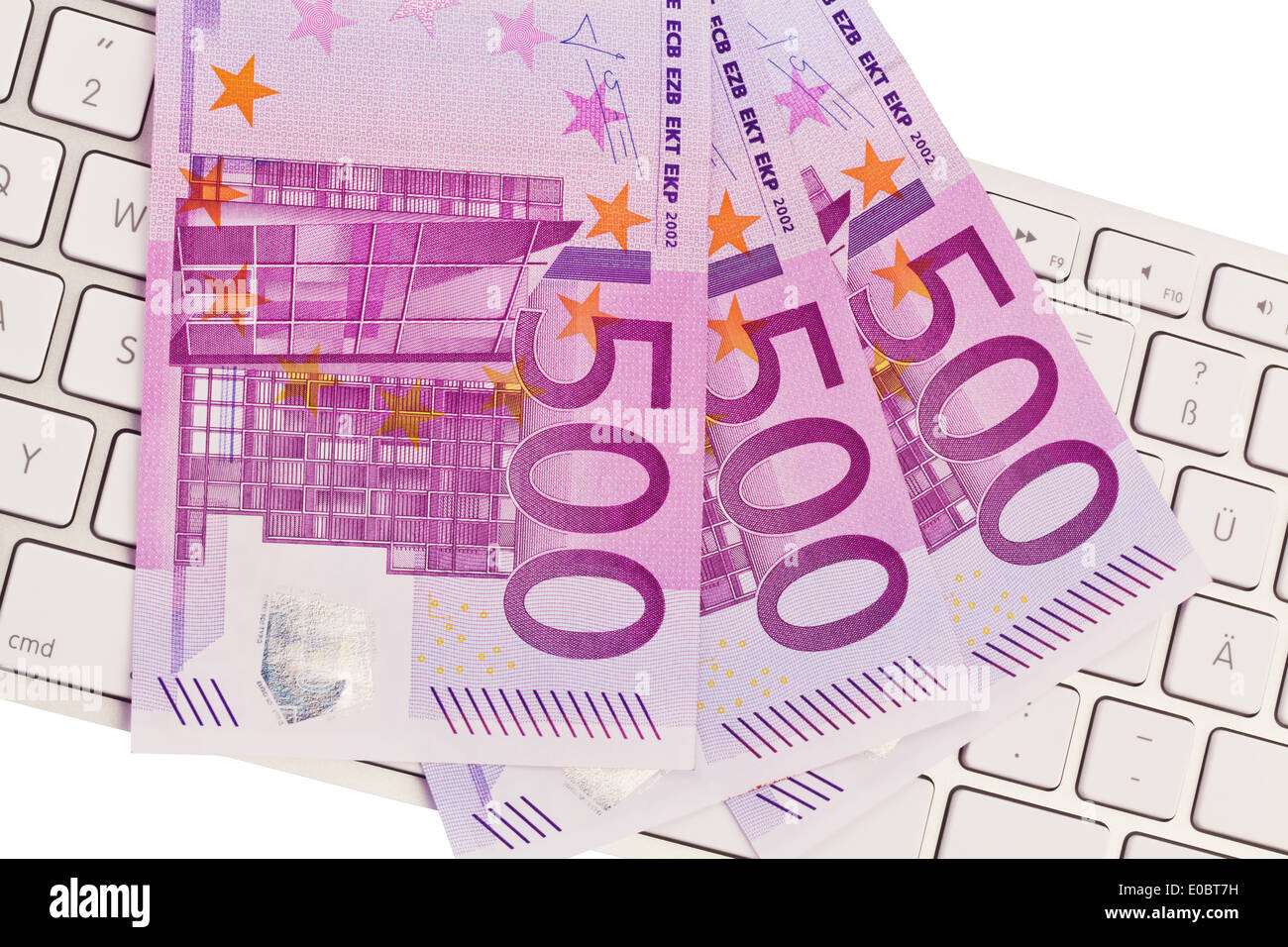 A lot of 500 euromoney bank notes lies on a pile. On a computer keyboard, Viele 500 Eurogeld Banknoten liegen auf Stock Photo