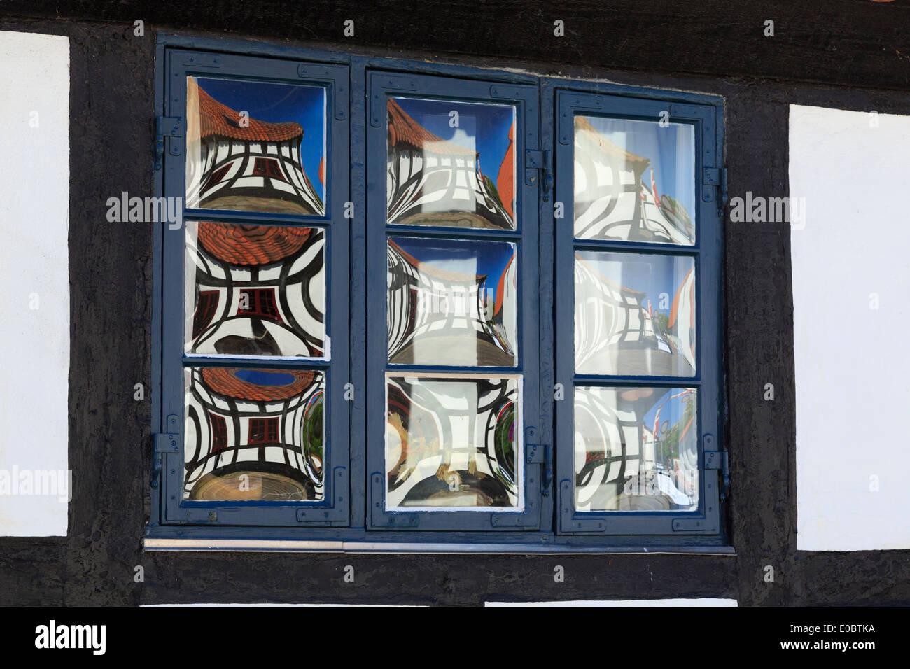 Quaint old glass window panes detail reflecting timbered house in Ebeltoft, Jutland, Denmark, Scandinavia, Europe - Stock Image