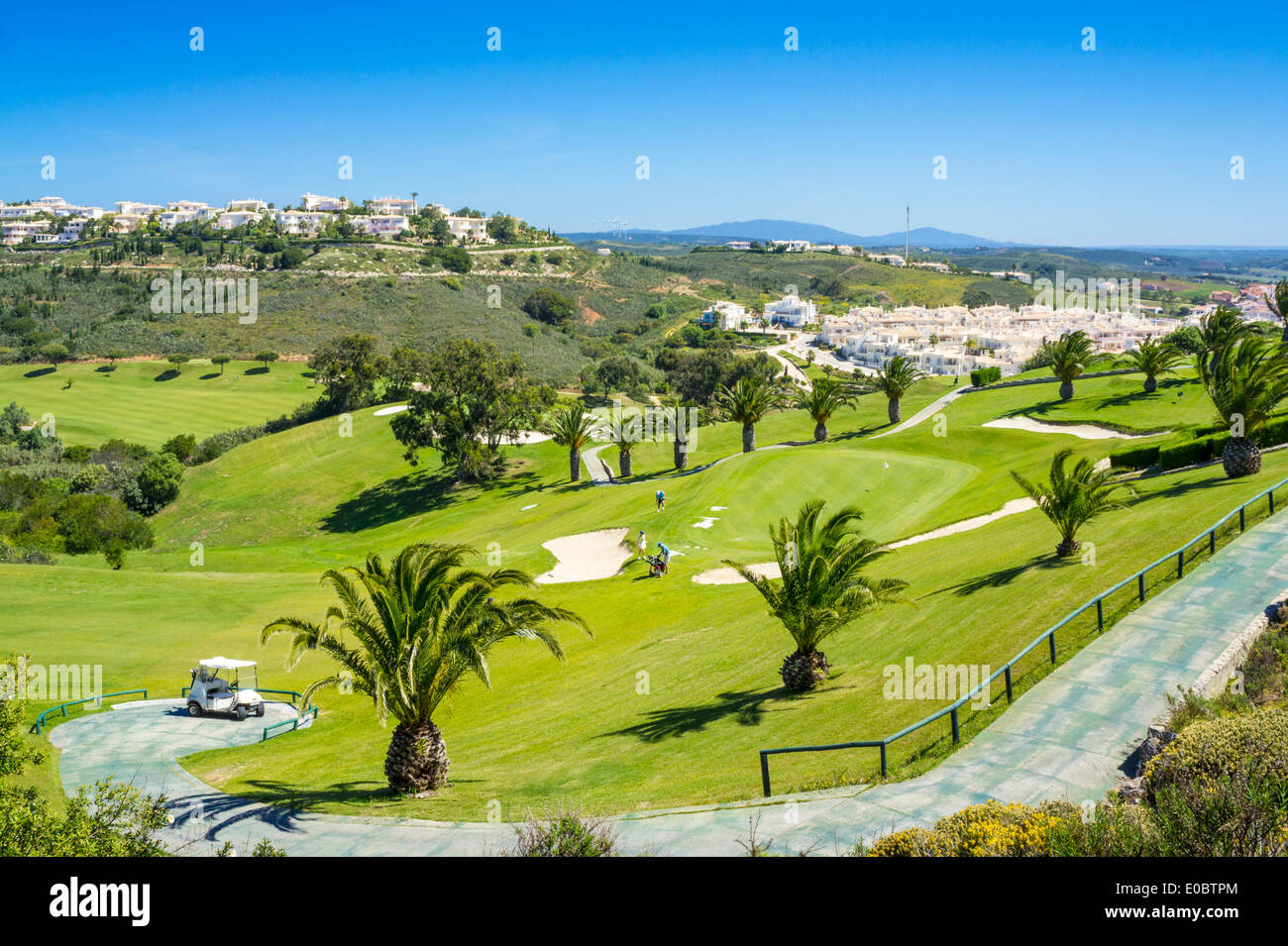 Golf buggy parked at the first hole and fairway Parque da Floresta golf course Vale do Poco Budens  near Salema Algarve Portugal - Stock Image
