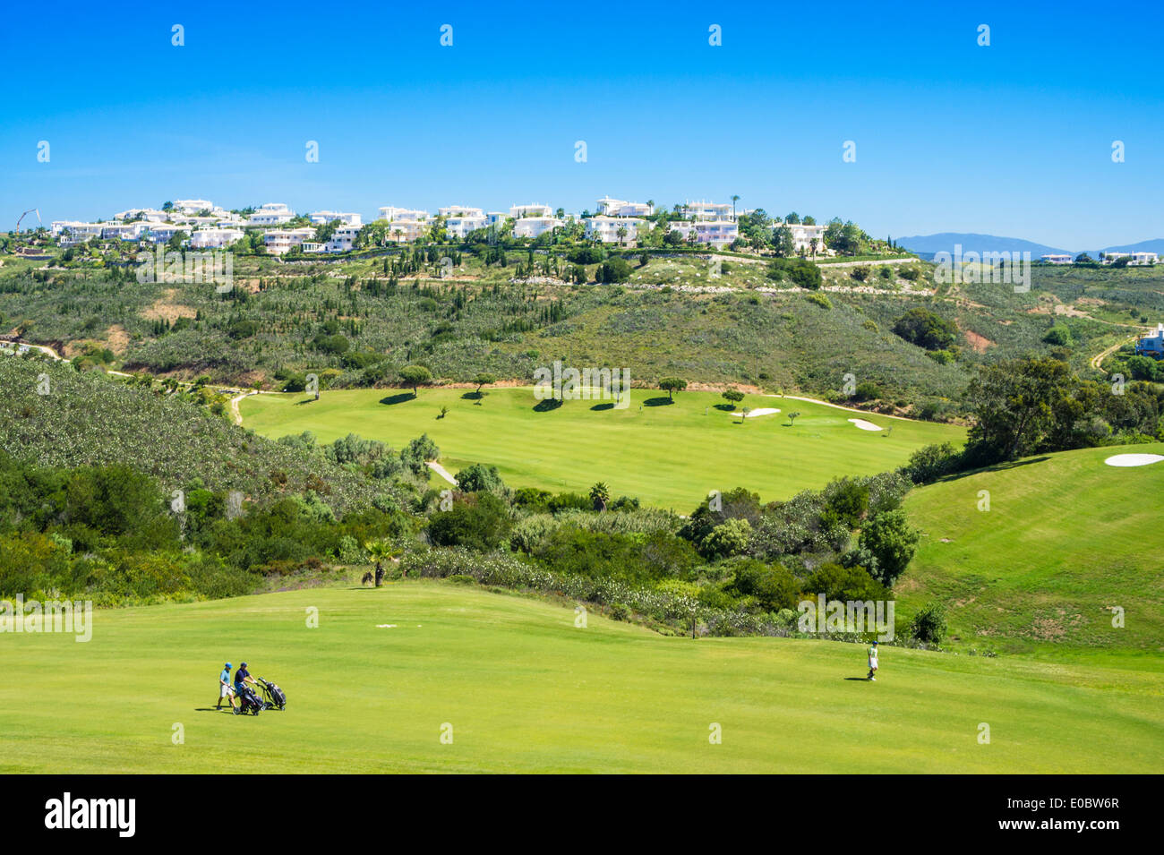 Golfers playing golf o0n the first fairway at Parque da Floresta golf course Vale do Poco Budens  near Salema Algarve Portugal - Stock Image