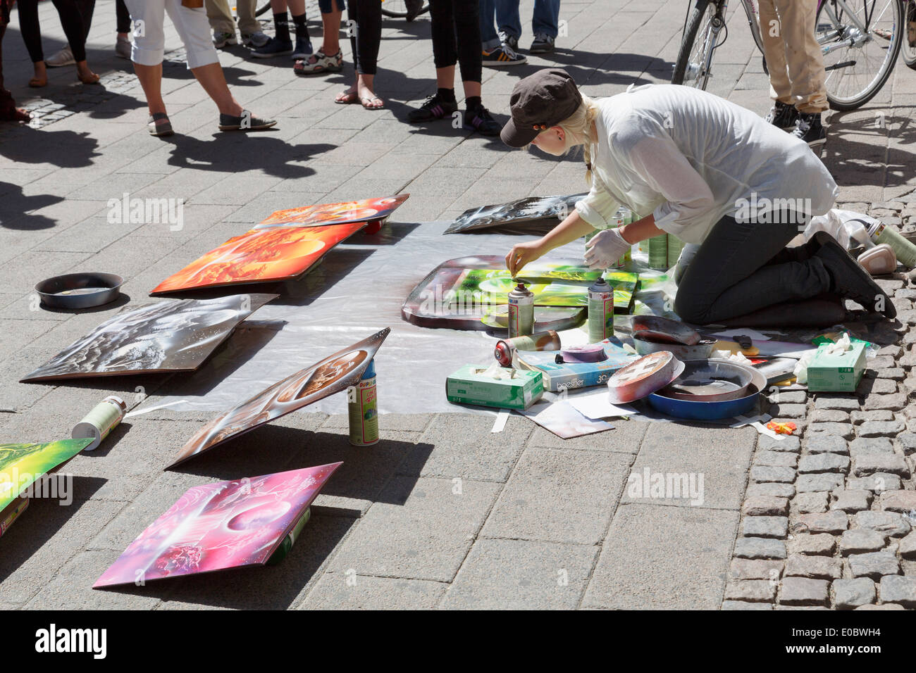Spray paint street artist painting pictures to sell with an audience watching in Copenhagen, Denmark, Scandinavia, Europe. - Stock Image