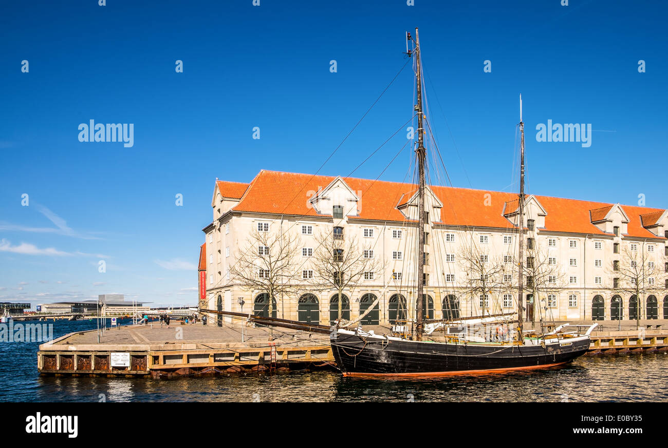 An old wooden ship in front of Eigtveds Pakhus, Conference center, Copenhagen, Denmark - Stock Image