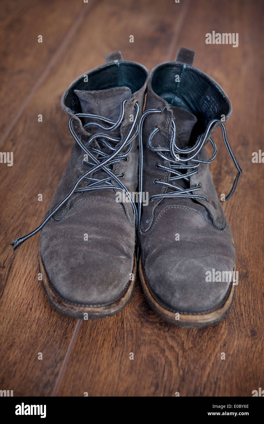 A pair of grey suede man's lace-up boots on a wooden floor. - Stock Image