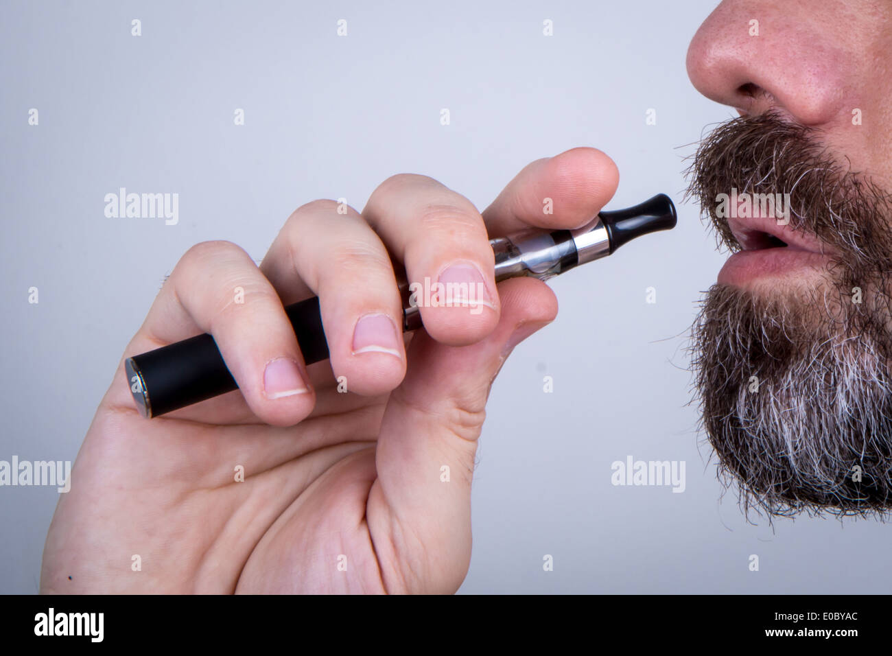 Bearded man using a vaporiser - Stock Image