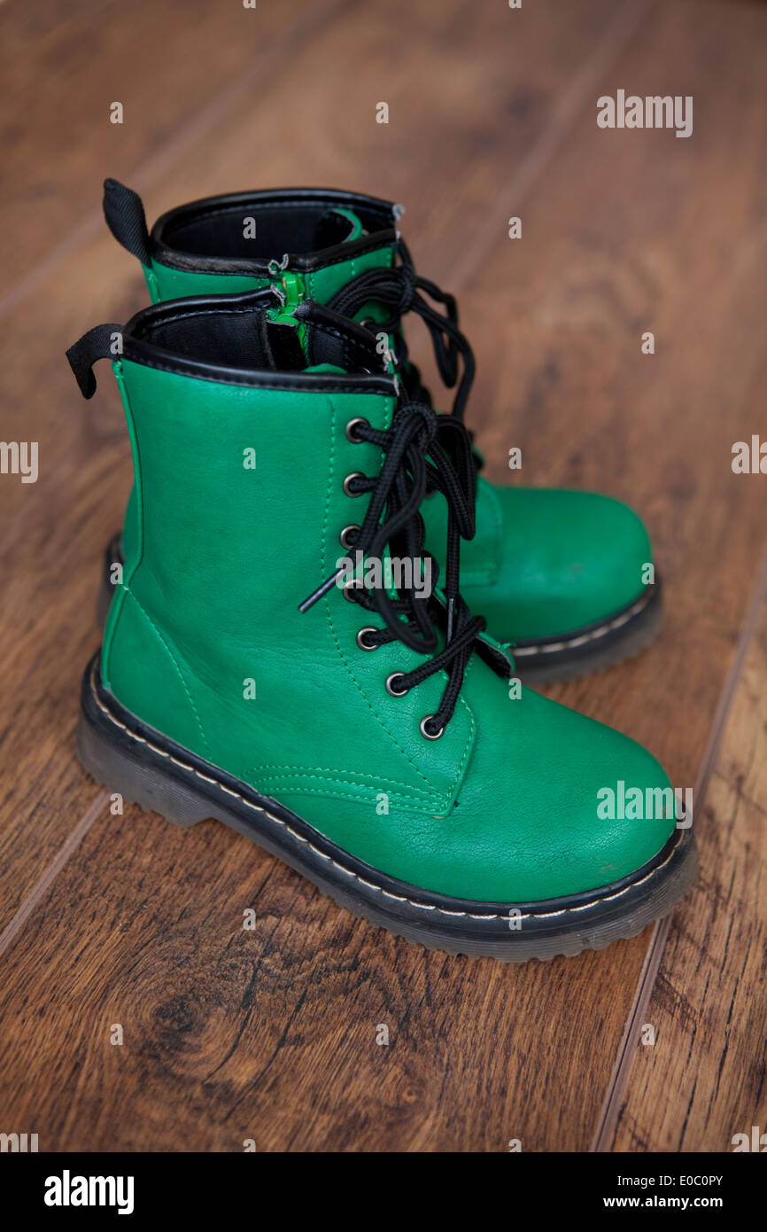 A pair of green lace-up boots on a wooden floor. - Stock Image