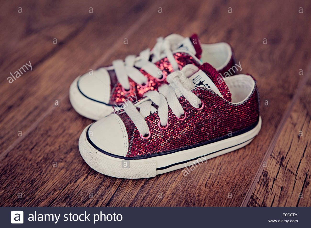 A pair of small, red, baby Converse shoes on a wooden floor. - Stock Image