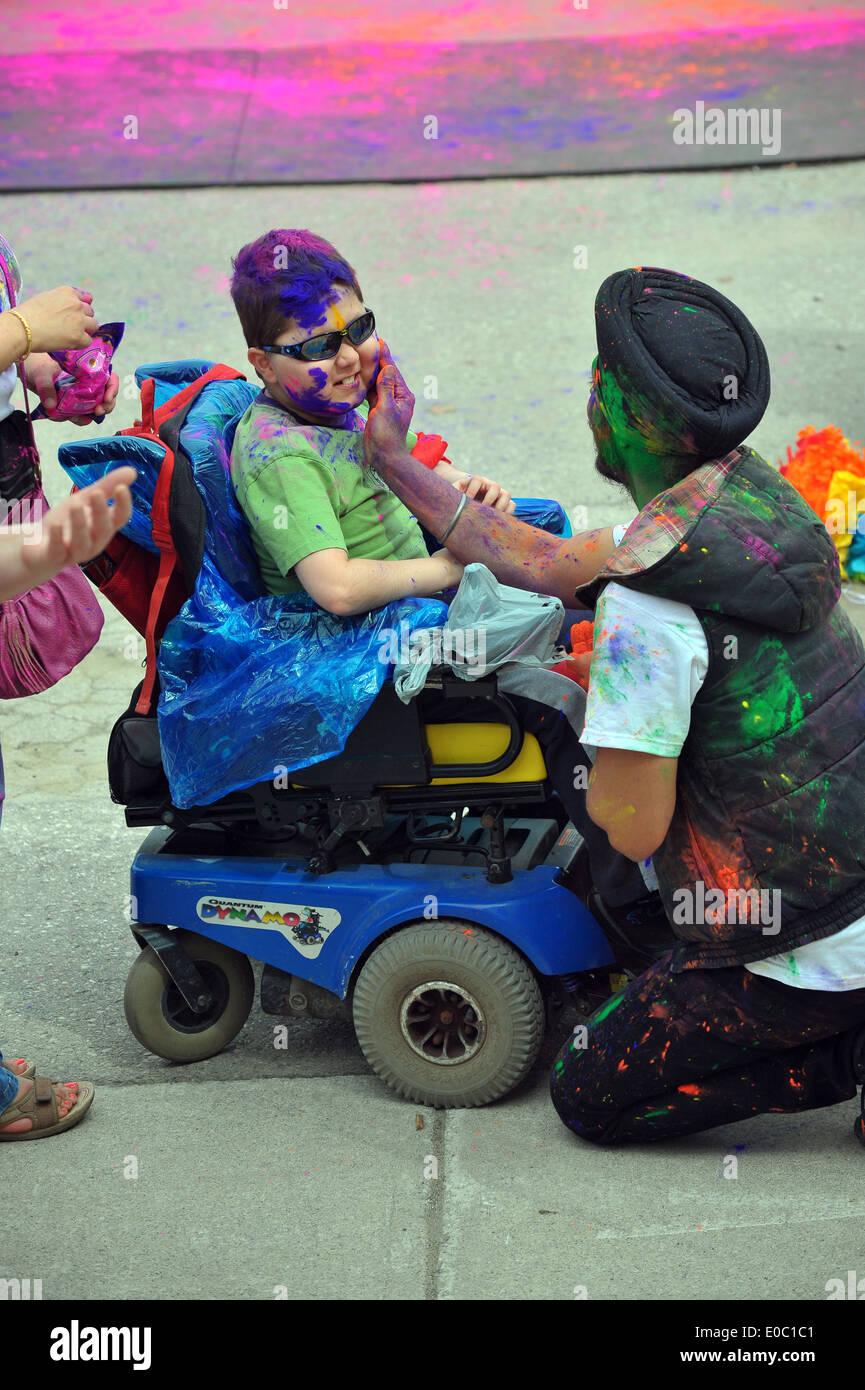 Canadians participate in the annual Spring Holi Festival by throwing coloured powder, dancing, chanting and singing. - Stock Image