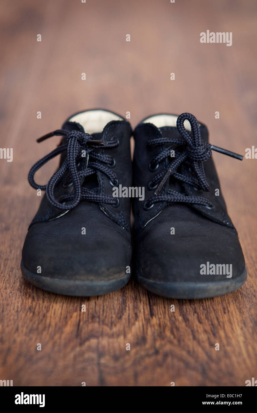 Baby boots on a wooden floor. - Stock Image