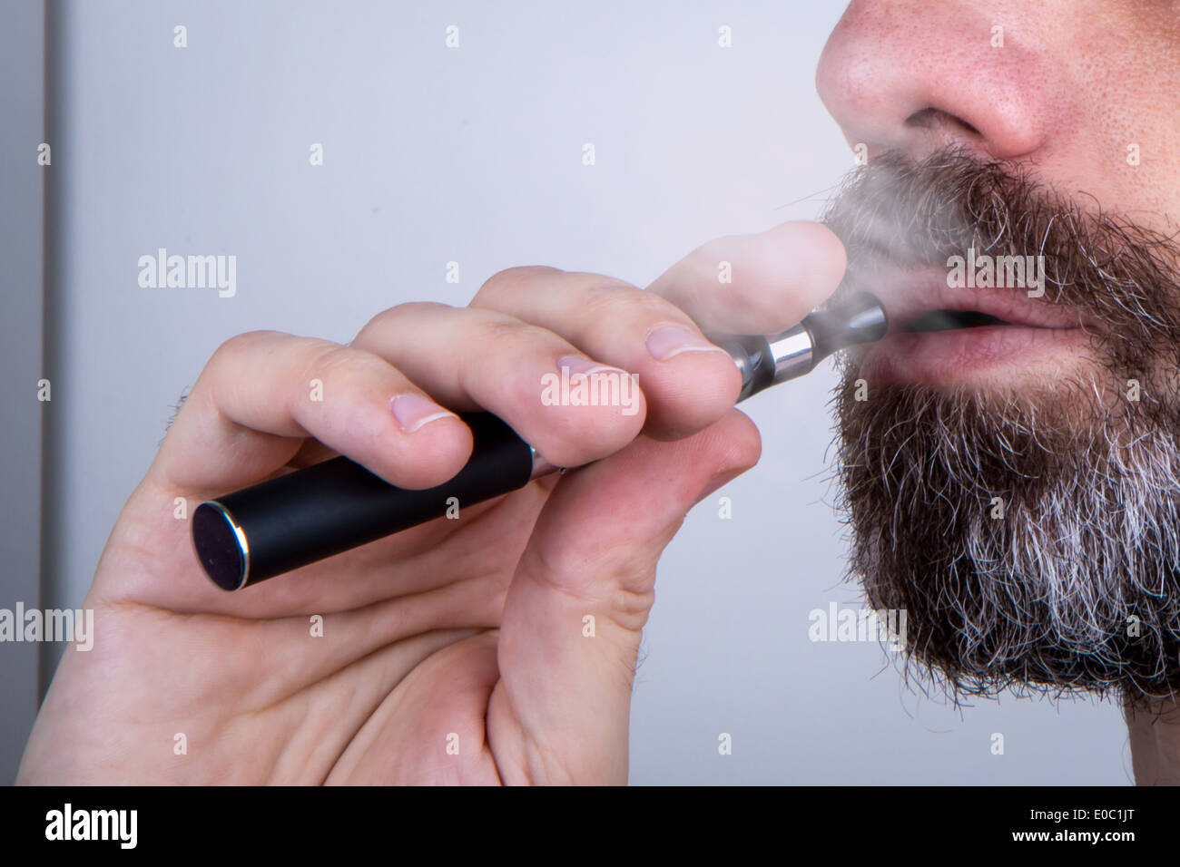 Bearded man using a vaporiser (with vapor) - Stock Image