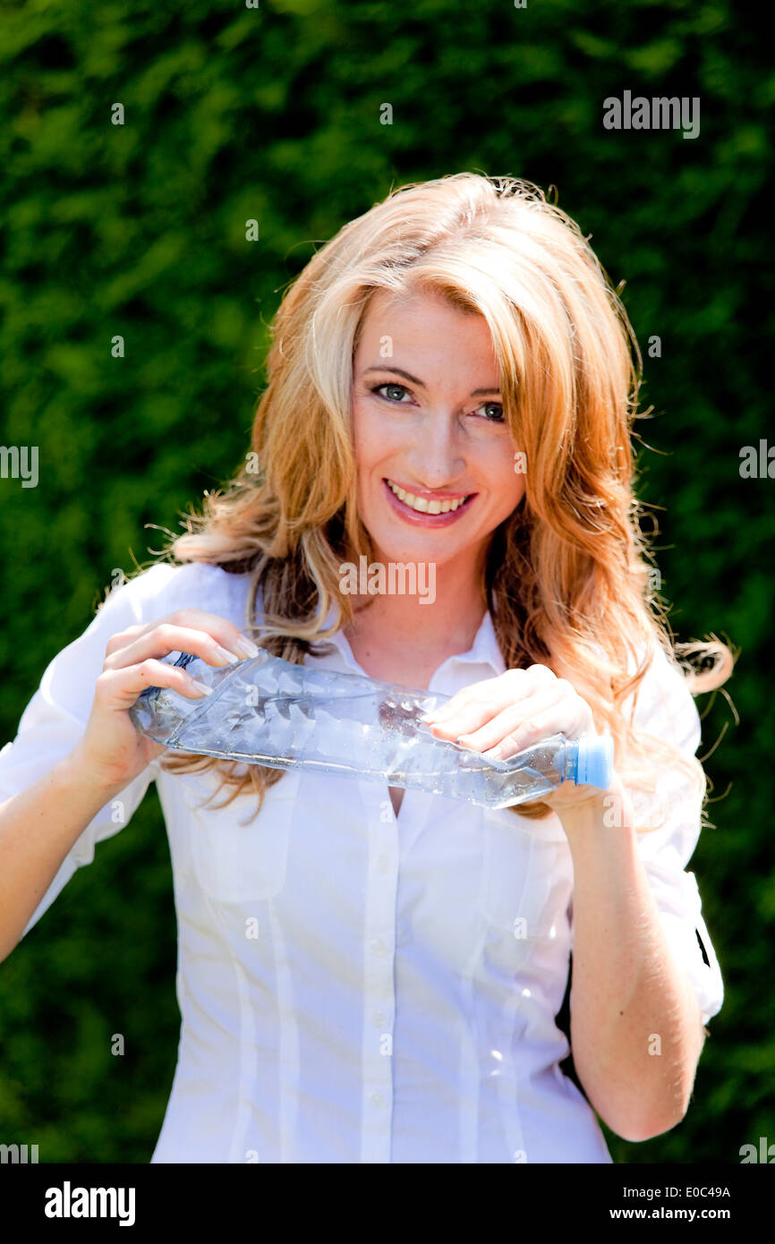 Woman with plastic bottle with garbage separation. Environmentally sound disposal, Frau mit Plastikflasche bei Muell Stock Photo