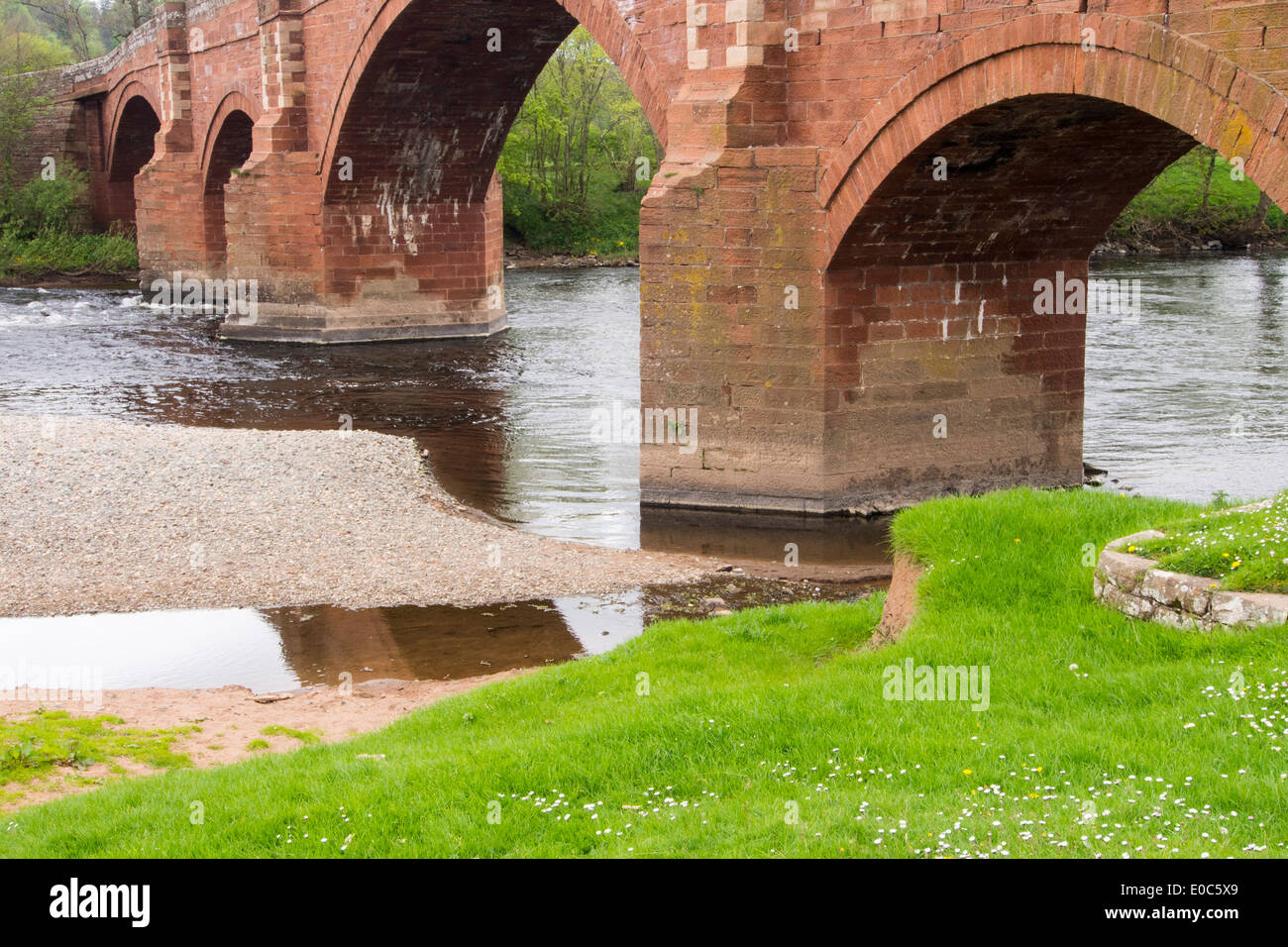 An old red sandstone bridge across the river Eden at Kirkoswold, Cumbria, UK. - Stock Image