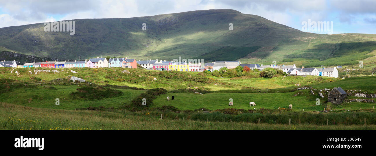 Sheep grazing in a field and colourful houses; Allihies, County Cork, Ireland - Stock Image