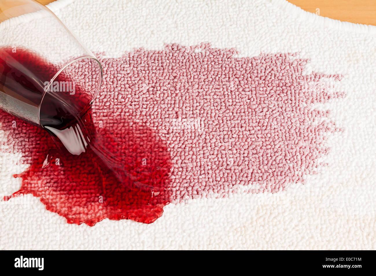 Red wine is tipped out on a carpet. Umgeleertes glass, Roter Wein wird auf einem Teppich ausgeschuettet. Umgeleertes Stock Photo