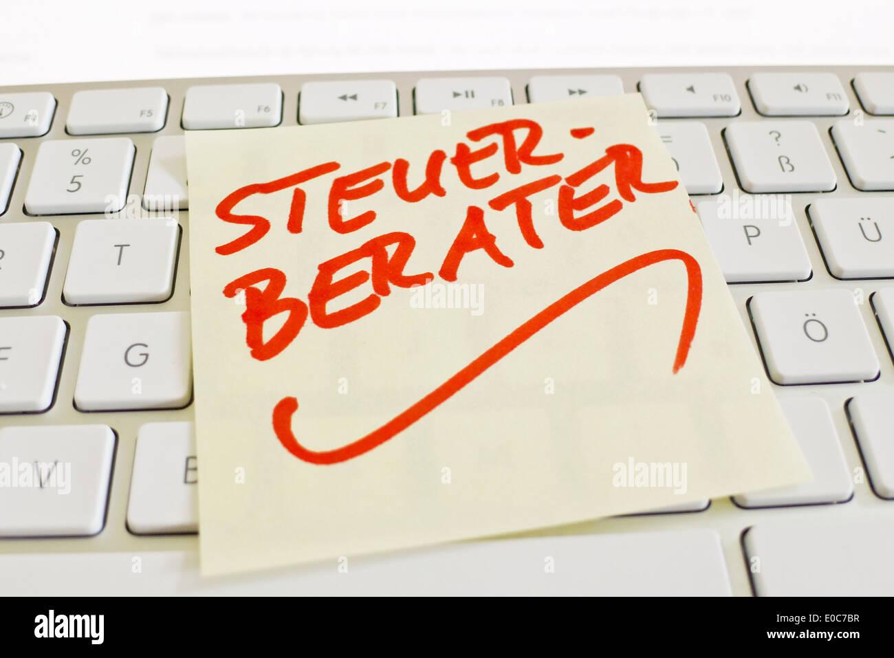 A note slip of paper lies on the keyboard of a computer in memory: Tax adviser, Ein Notizzettel liegt auf der Tastatur Stock Photo