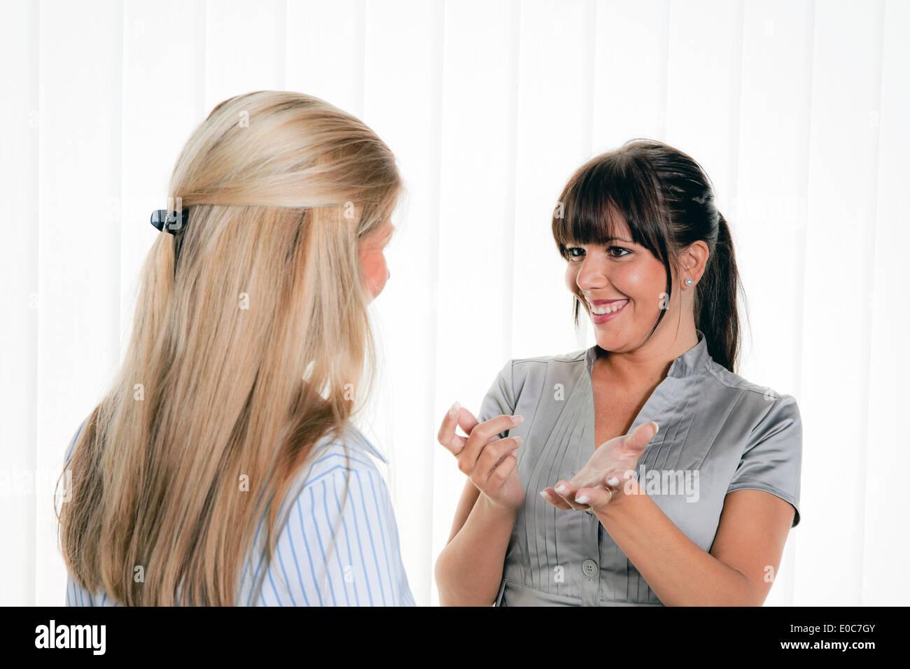 Two women in the conversation on the place Arbits in the office, Zwei Frauen beim Gespraech am Arbitsplatz im Buero - Stock Image