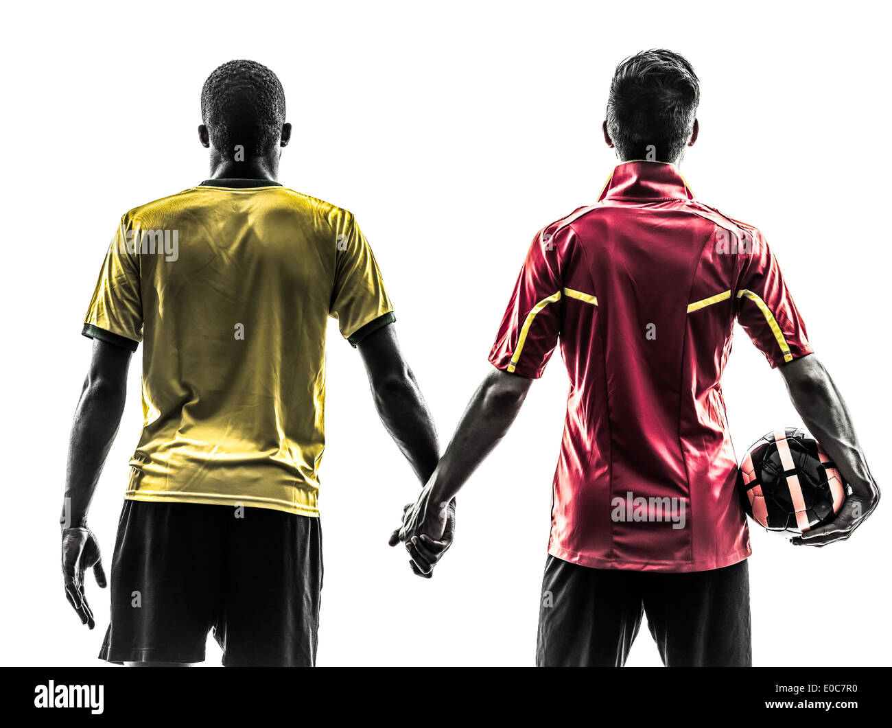 two men soccer player playing football competition hand in hand in silhouette on white background - Stock Image