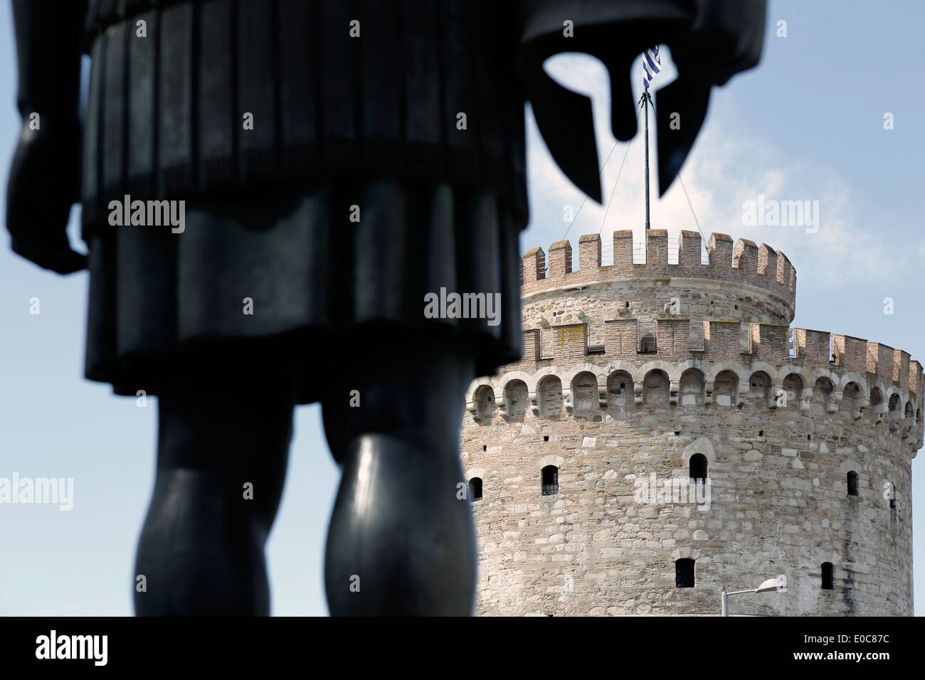 White Tower (Lefkos Pirgos), the landmark of northern Greek city of Thessaloniki as seen behind a Macedonian warrior. - Stock Image