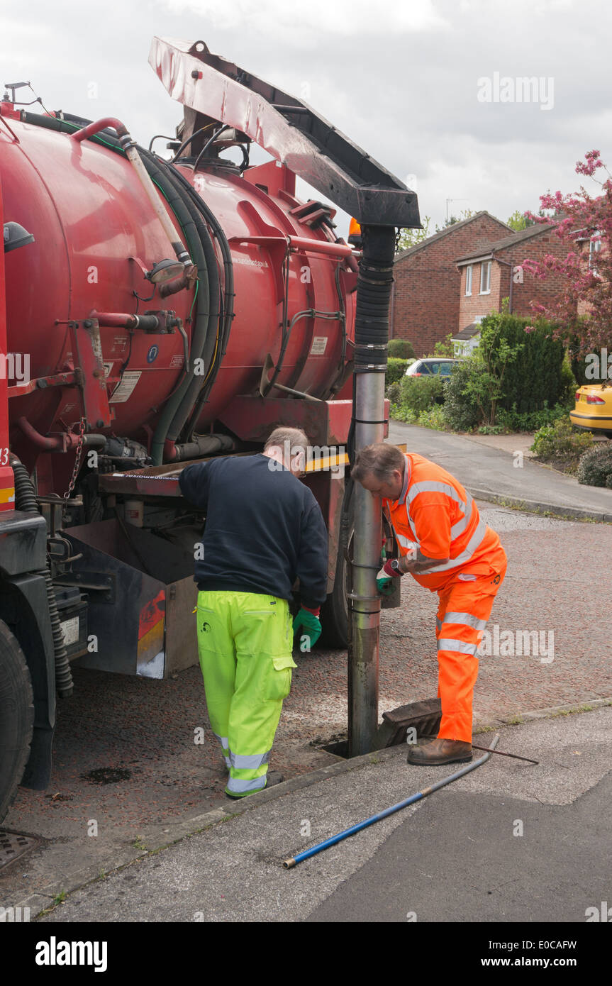 Workmen cleaning out road drains using a 'Gulley Sucker' or Gully Emptier suction tank truck, north east England UK - Stock Image