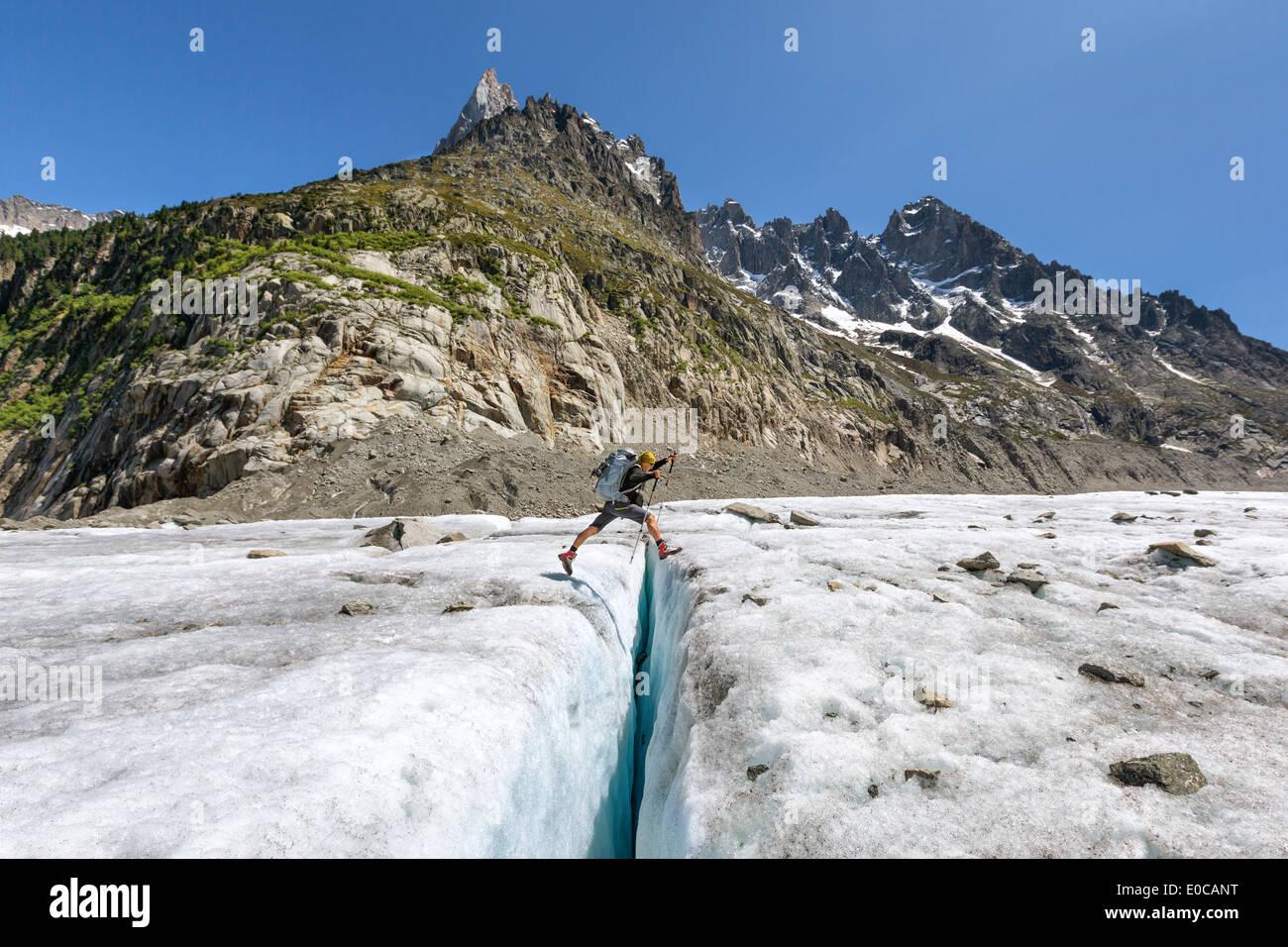 Leaping over crevasse at Mer de Glace glacier, Chamonix, Alps, France, EU - Stock Image