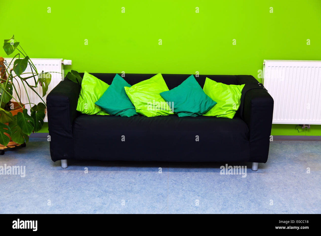A Black Sofa In A Sitting Room Before A Green Wall, Eine Schwarzes Sofa In