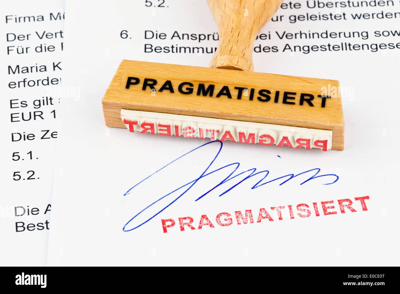 A stamp of wood lies on a document. Label Tenured, Ein Stempel aus Holz liegt auf einem Dokument. Aufschrift Pragmatisiert Stock Photo