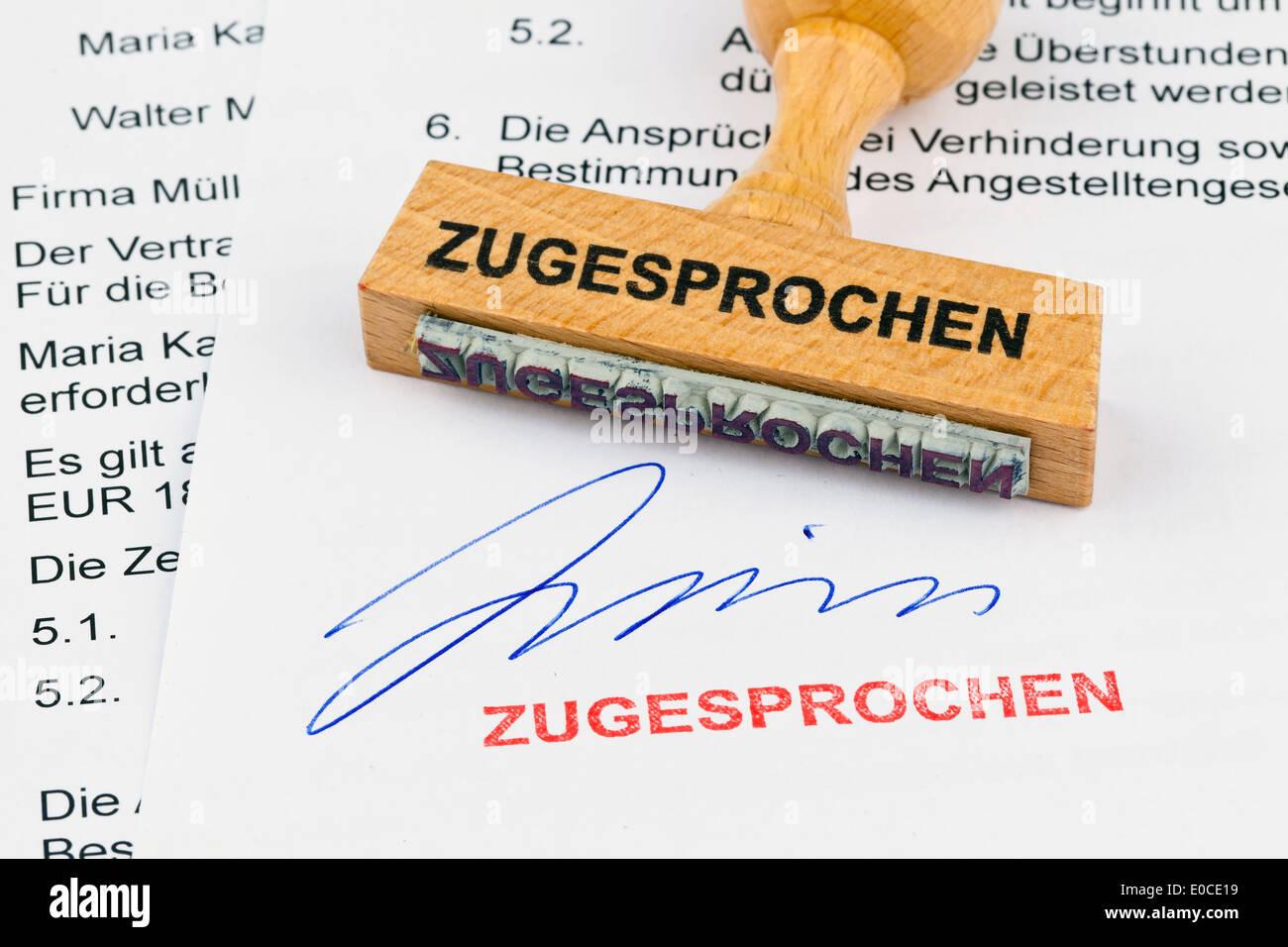A stamp of wood lies on a document. Label Awarded, Ein Stempel aus Holz liegt auf einem Dokument. Aufschrift Zugesprochen Stock Photo