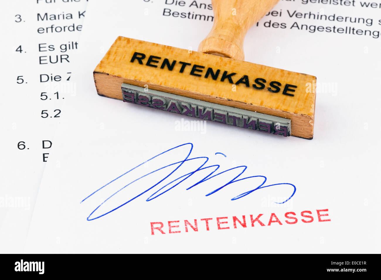 A stamp of wood lies on a document. Label Pension fund, Ein Stempel aus Holz liegt auf einem Dokument. Aufschrift Rentenkasse Stock Photo