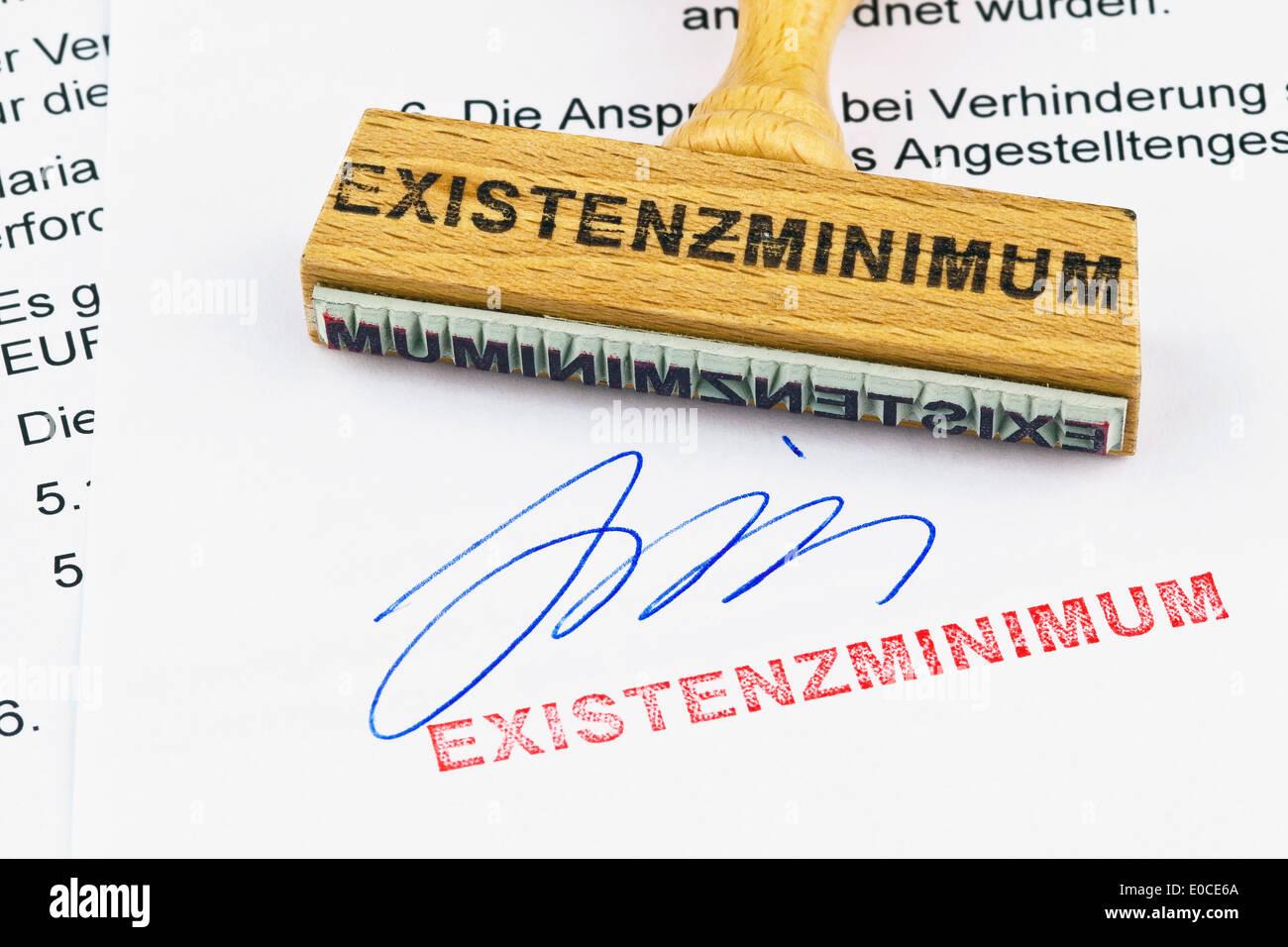 A stamp of wood lies on a document. Label Subsistence level, Ein Stempel aus Holz liegt auf einem Dokument. Aufschrift Existenzm - Stock Image