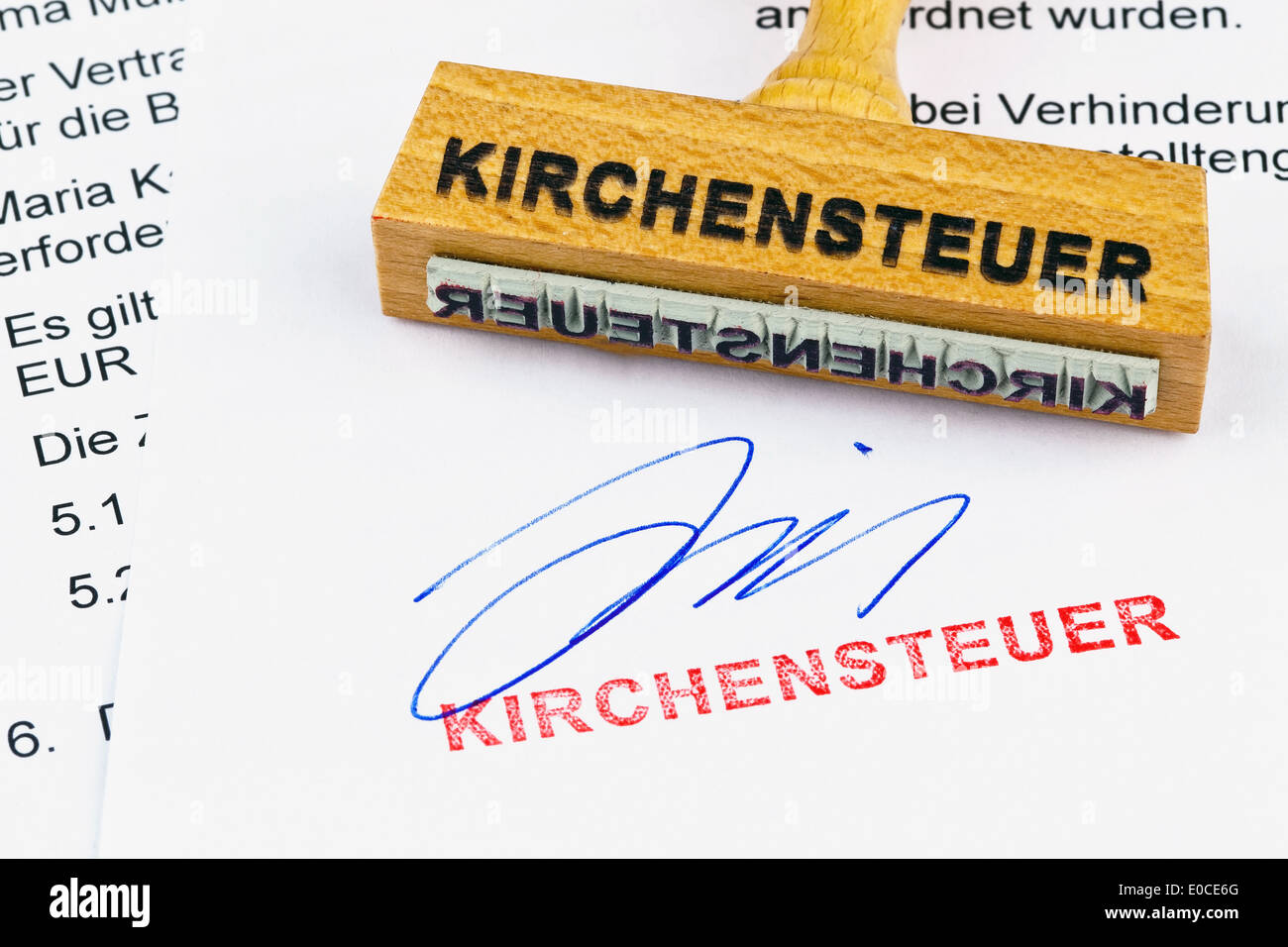 A stamp of wood lies on a document. Label Church-expensive, Ein Stempel aus Holz liegt auf einem Dokument. Aufschrift Stock Photo
