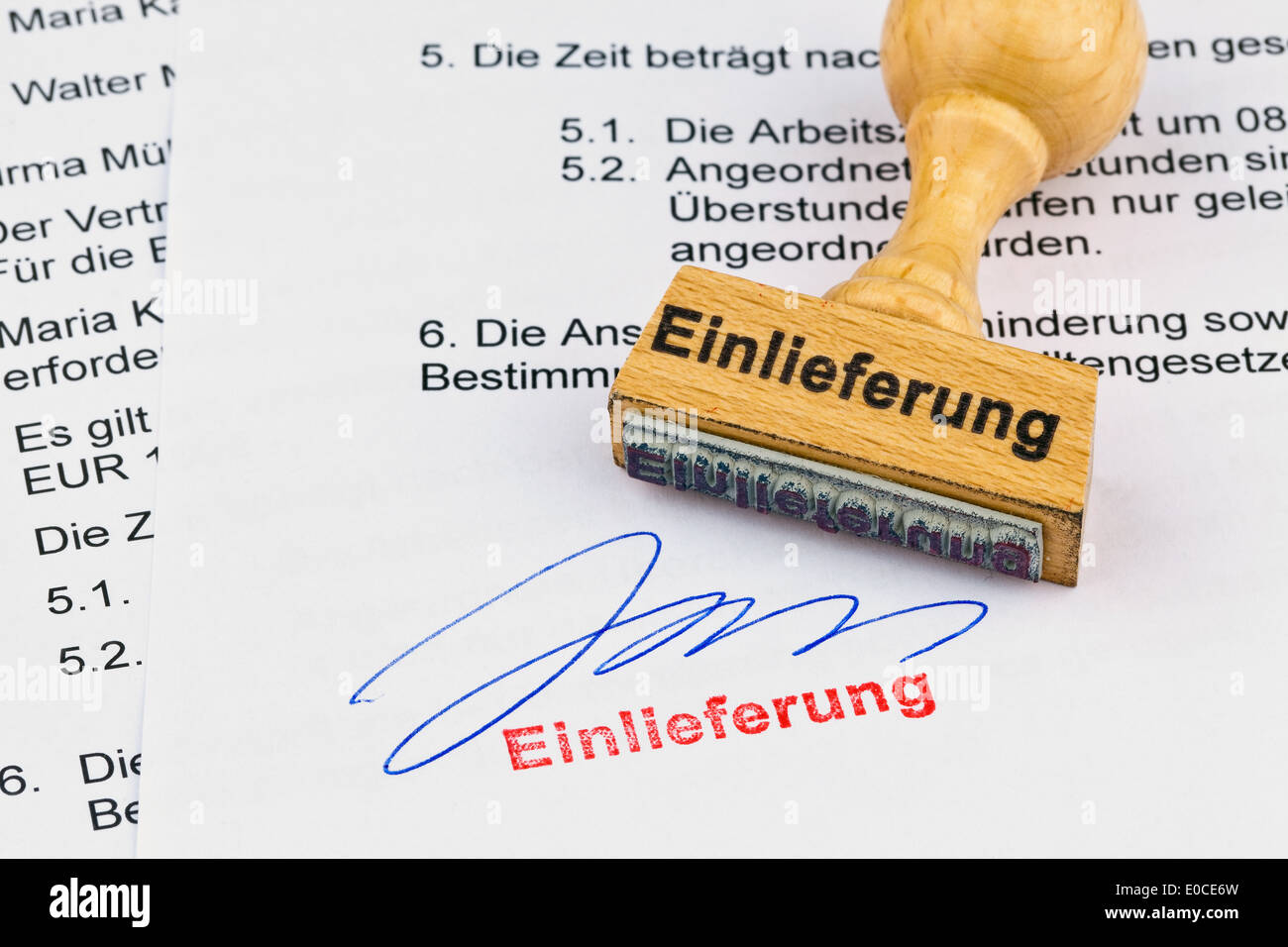 A stamp of wood lies on a document. Label Admission, Ein Stempel aus Holz liegt auf einem Dokument. Aufschrift Einlieferung Stock Photo