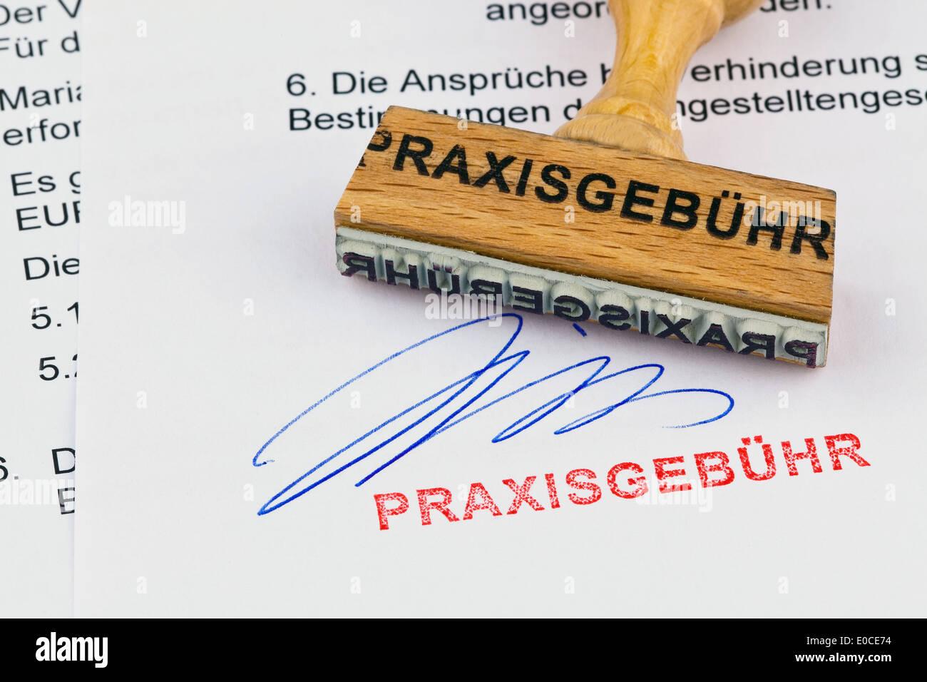 A stamp of wood lies on a document. Label Practise fee, Ein Stempel aus Holz liegt auf einem Dokument. Aufschrift Stock Photo