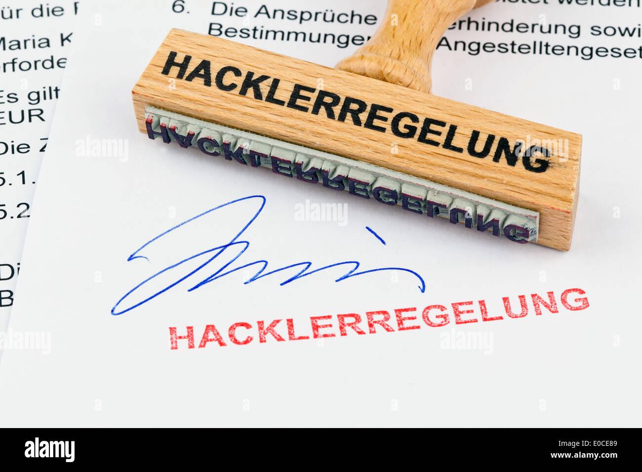 A stamp of wood lies on a document. Label Hacklerregelung, Ein Stempel aus Holz liegt auf einem Dokument. Aufschrift Hacklerrege Stock Photo