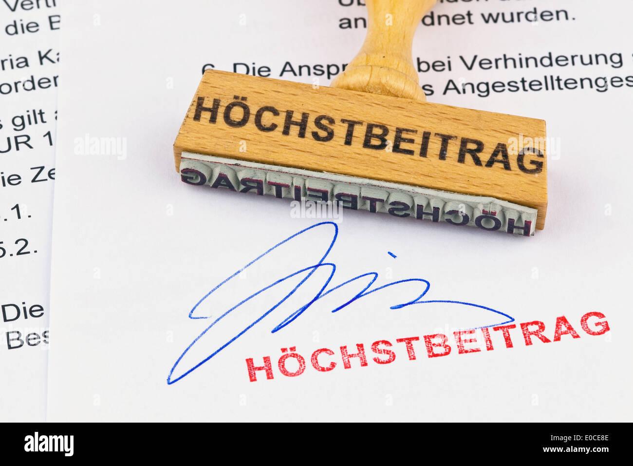 A stamp of wood lies on a document. Label Hoechstbeitrag, Ein Stempel aus Holz liegt auf einem Dokument. Aufschrift Stock Photo