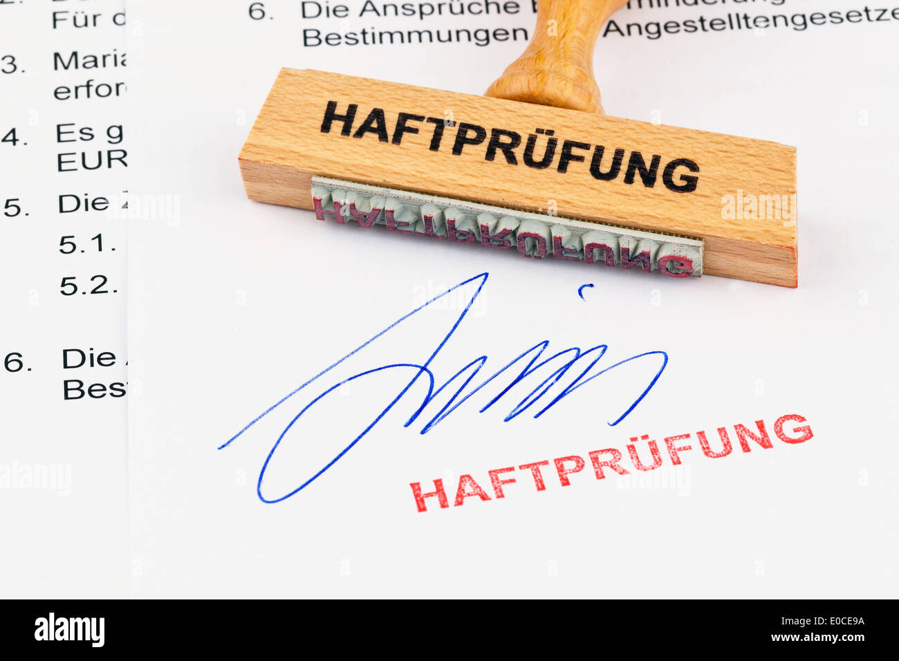 A stamp of wood lies on a document. Label Custody check, Ein Stempel aus Holz liegt auf einem Dokument. Aufschrift Stock Photo
