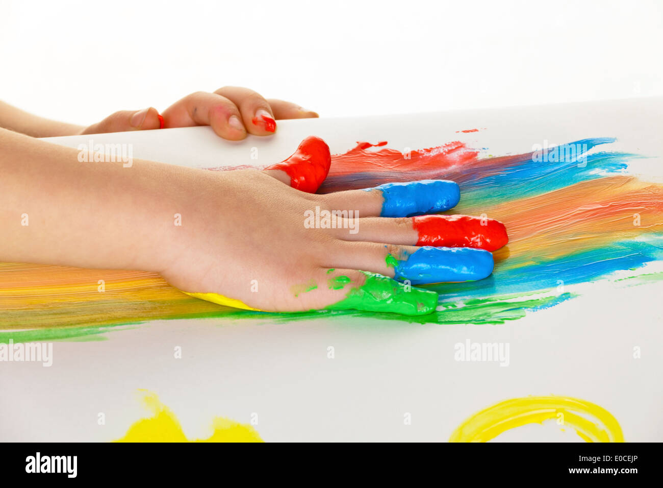 A small child paints with fingerpaints. Funnily and Creatively., Ein kleines Kind malt mit Fingerfarben. Lustig und Kreativ. - Stock Image