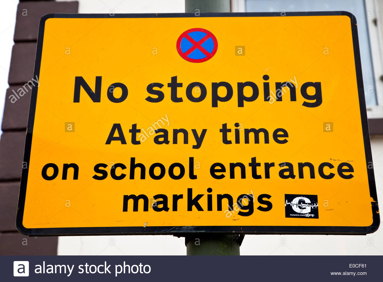Yellow sign 'No stopping at any time on school markings' - Stock Image
